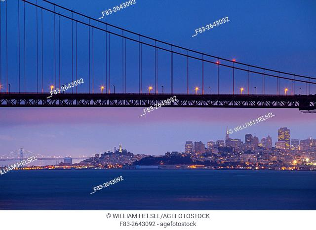 San Francisco, CA, USA: city skyline, Golden Gate Bridge, Bay Bridge, Coit Tower, Fisherman's Wharf, high-rise office buildings, dusk, view from Kirby Cove