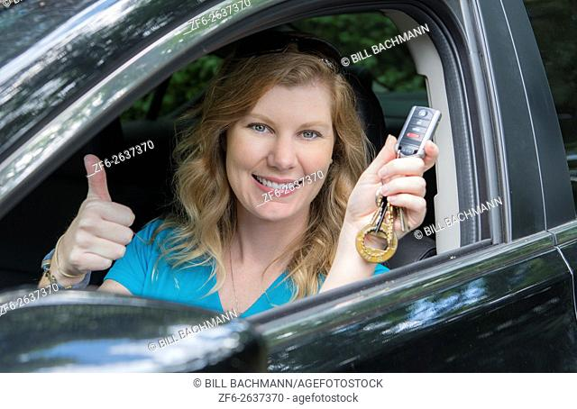 Young teenage girl age 16 with first driving of a car showing off her keys MR model released