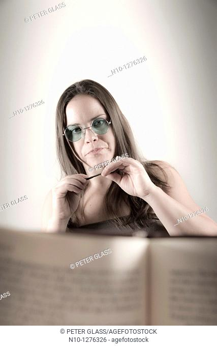 Young woman seen from behind a book