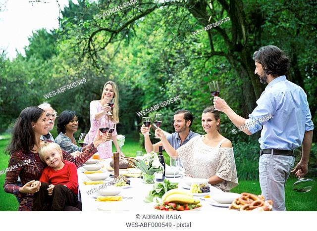 Man toasting with red wine on a garden party