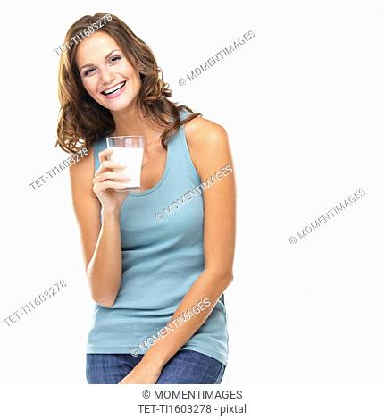 Studio portrait of attractive young woman smiling and holding glass of milk