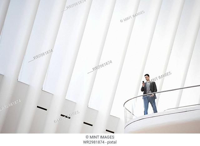 A person standing alone in an atrium by a railing, in the Oculus building under a high white ridged ceiling