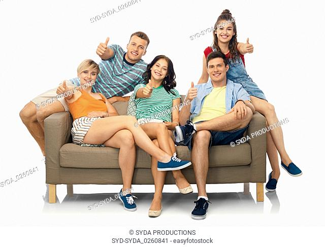 friends sitting on sofa and showing thumbs