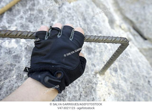 Hand of a man with climbing gloves holding on an iron bar of a via ferrata