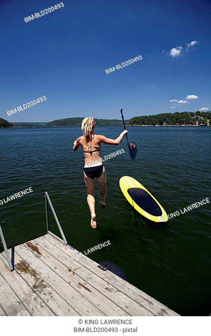 Caucasian woman jumping in lake next to paddleboard