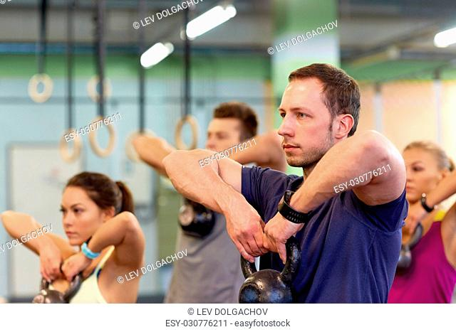 sport, fitness, weightlifting and training concept - group of people with kettlebells and heart-rate trackers exercising in gym