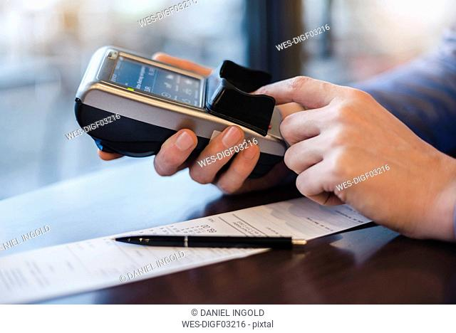 Man using credit card reader, close-up