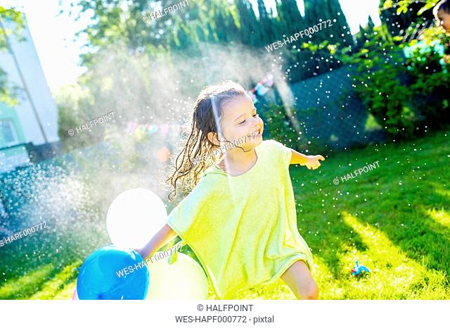 Little girl with balloons having fun with lawn sprinkler in the garden