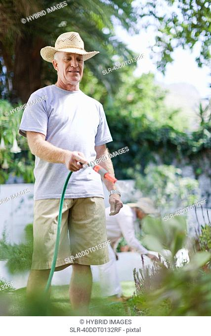 Older man watering plants in backyard
