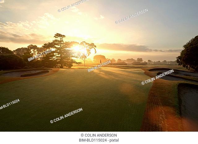 Sun rising over golf course
