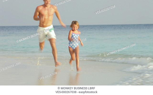 Father chases daughter along beach before picking her up and swinging her in arms.Shot on Canon 5d Mk2 with a frame rate of 30fps