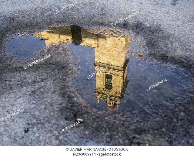 Tower of the Santos Juanes church reflected in a puddle, Valencia, Spain