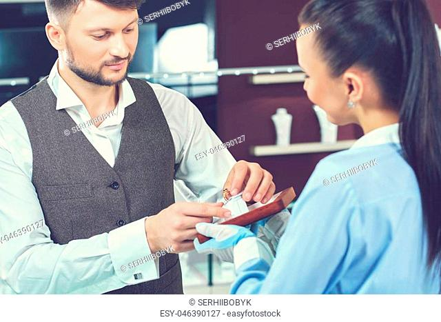 Showing an assortment. Handsome young man choosing engagement ring at the jewelry store with the help of a professional jeweler shopping buying consumerism...