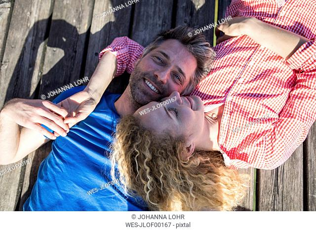 Happy affectionate couple lying on jetty