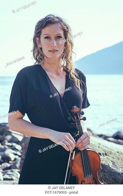 Portrait of beautiful woman holding violin while standing at lakeshore
