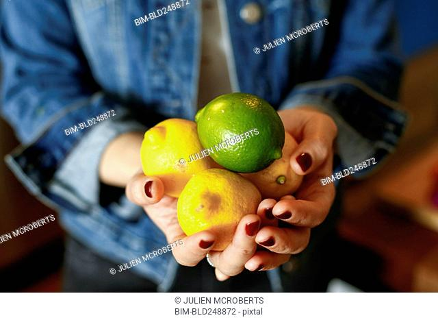 Hands of woman holding lemons and lime