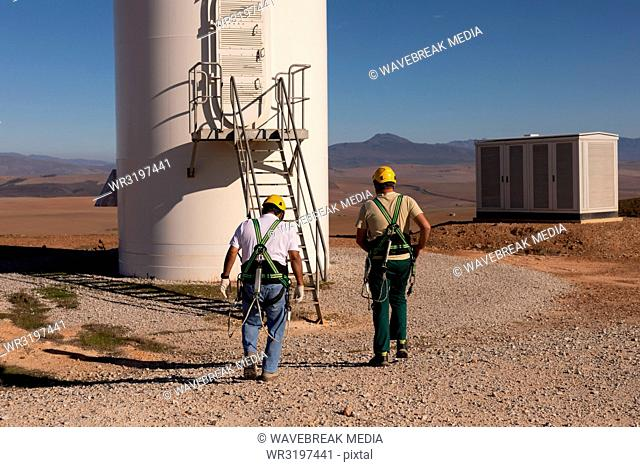 Engineers walking toward a wind mill at a wind farm