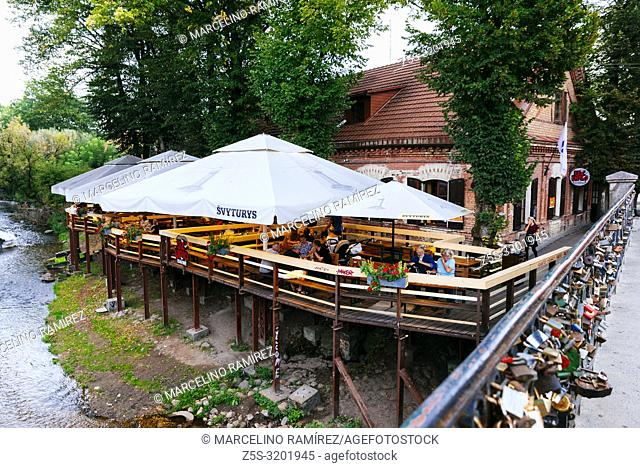 Lively terrace over the river Vilnia. Uzupis is a neighborhood in Vilnius, on April 1, 1997, the district declared itself an independent republic