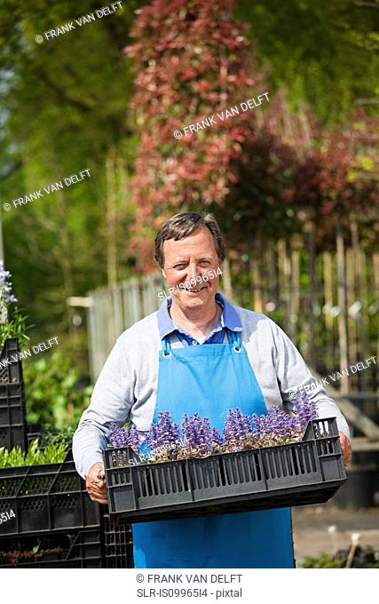Man carrying crate of flowers, portrait