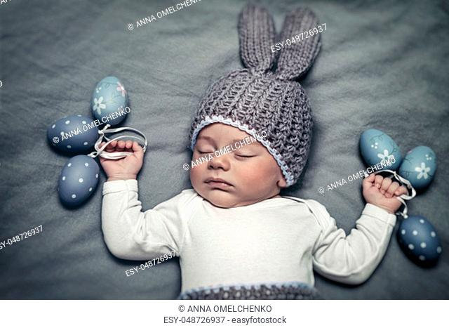 Portrait of a cute little baby boy wearing bunny costume and holding decorative eggs in hands, happy Easter holiday