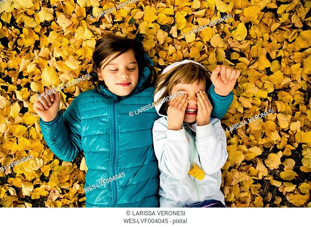 Two girls lying side by side on ground covered with autumn leaves