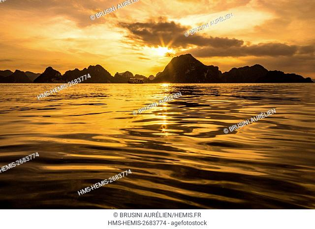 Vietnam, Gulf of Tonkin, Quang Ninh province, Ha Long Bay (Vinh Ha Long) listed as World Heritage by UNESCO (1994), sunset on the iconic landscape of karst...