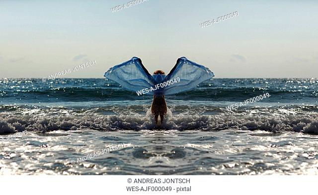 Silhouette of young woman in front of the sea holding blue cloth with outstretched arms