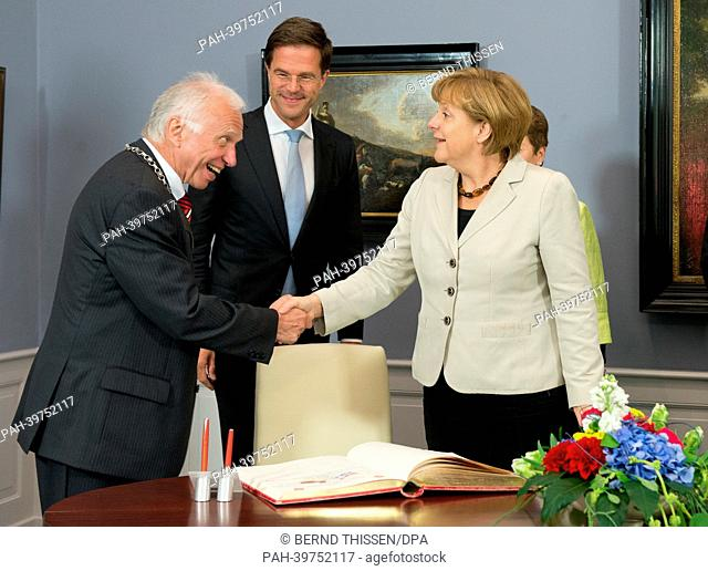 Mayor of Kleve (L-R) Theodor Brauer greets Dutch Prime Minister Mark Rutte and German Chancellor Angela Merkel take part in the first German-DutchCabinet...