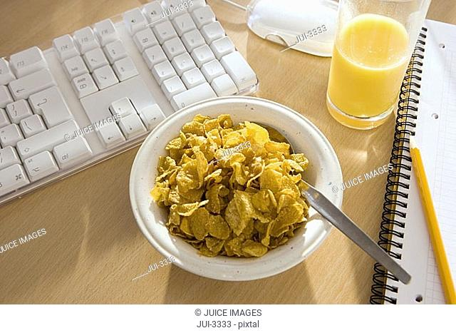 Bowl of cornflakes and glass of orange juice on office desk, close-up, elevated view still life