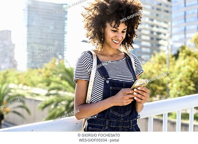 Young woman standing on a bridge, using smartphone