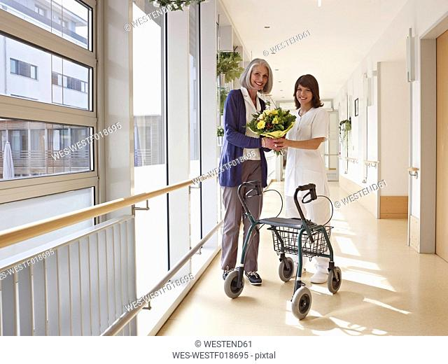 Germany, Cologne, Senior women and caretaker holding bouquet and standing by wheeled walker, smiling