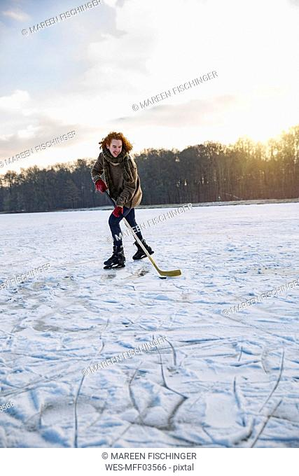 Man playing ice hockey on frozen lake