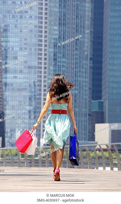 Rear view of woman walking with shopping bags, buildings in background