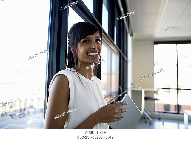 Smiling businesswoman holding digital tablet at office window