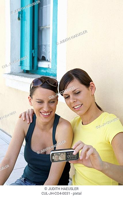 Two young girls outside a Greek House taking a self portrait with mobile smiling