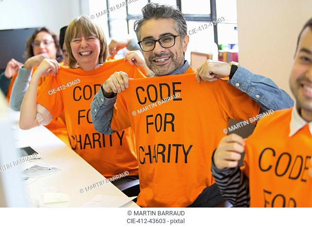 Portrait confident hackers in t-shirts coding for charity at hackathon