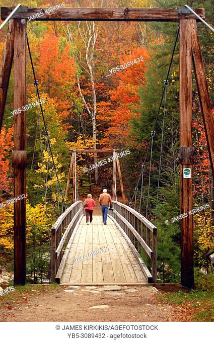 Two senior adults walk along a wooden pedestrian suspension bridge during fall in the White Mountains of New Hampshire