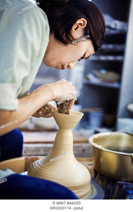 Woman working in a Japanese porcelain workshop, sitting at a potter's wheel, throwing bowl