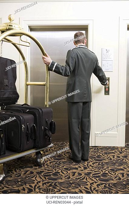 Bellhop with luggage cart waiting for elevator
