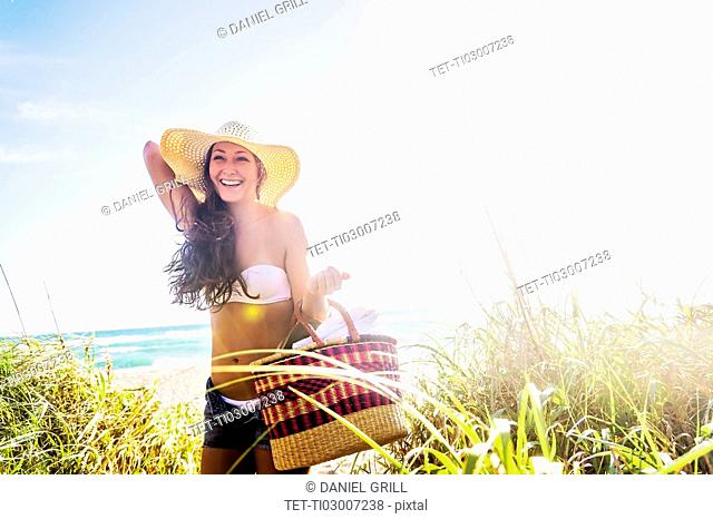 Woman in sunhat carrying basket on beach