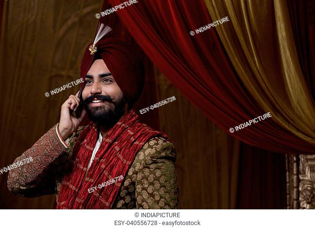 Close-up of groom having conversation on mobile phone
