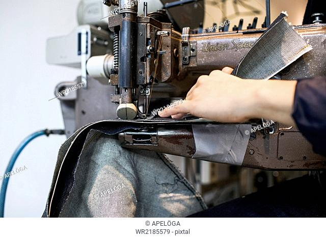 Cropped image of fashion designer sewing in jeans factory