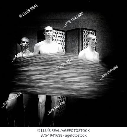 three naked male mannequins in a shop window