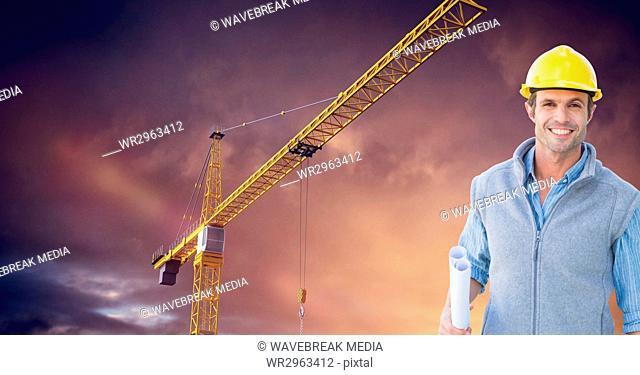 Smiling architect holding blueprints against crane