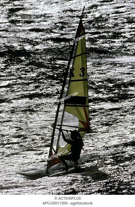 Single windsurfer cuts across waves at beach