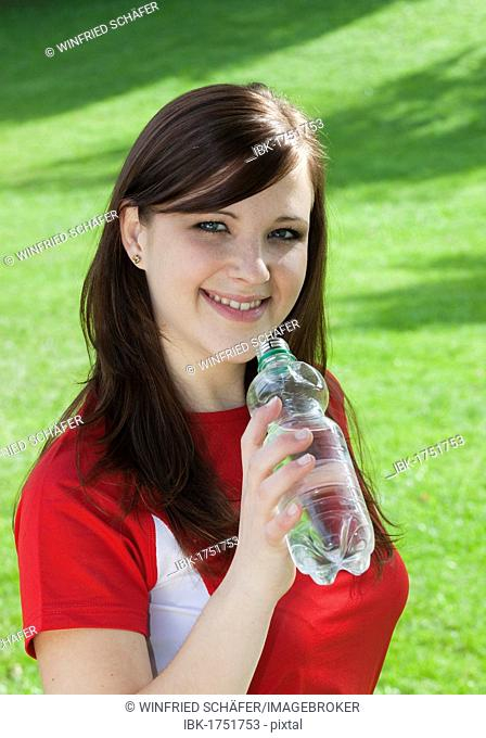 Young woman wearing sports clothing with a bottle of water in her hand