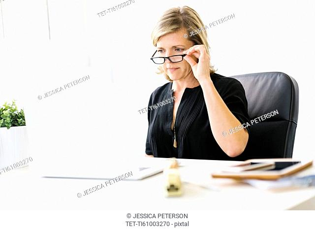 Mature woman in office touching her eyeglasses