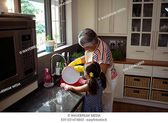 Grandmother and granddaughter washing utensil in kitchen sink
