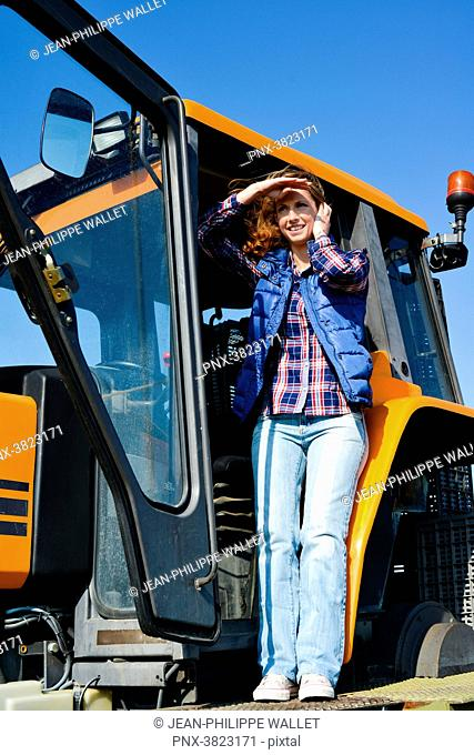 beautiful and cheerful young woman farmer driving tractor in the fields during harvest in countryside- Cepage Grenache