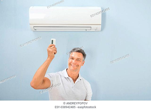 Portrait Of Mid-adult Man Using Air Conditioner